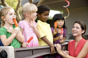 Group young preschool children playing in daycare with teacher