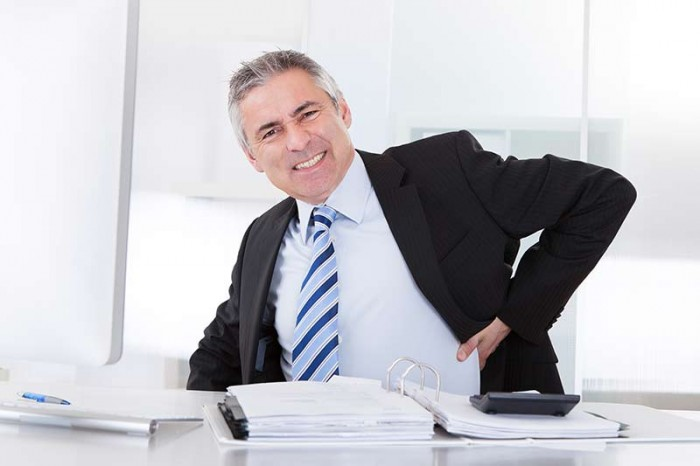 Man at desk with hurt back